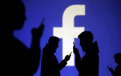 Silhouettes of mobile users are seen next to a screen projection of Facebook logo (Reuters)